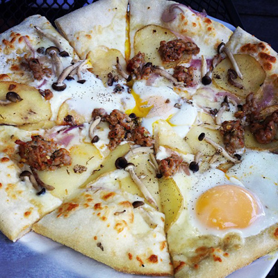 Breakfast Pizza with fennel sausage, roasted potatoes, mushrooms, caramelized onion, and two sunny side up eggs