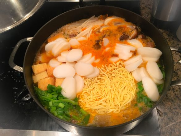 Budae Jjigae with the addition of instant ramen noodles, rice cakes, and green onion,