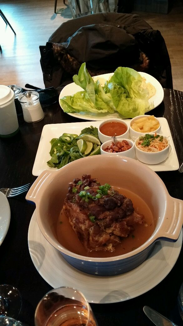 Lucky pig made of slow-roasted shoulder of homestead hampshire pork, & served with black sesame crepes, pickled pineapple, mongolian peanuts, & lettuce cups