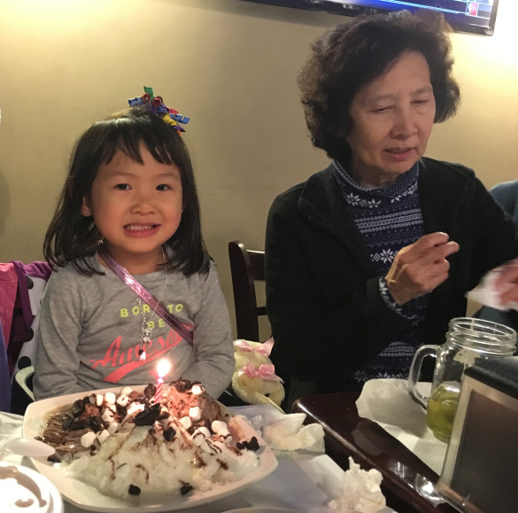 Roxy blowing out the candles on her shaved snow dessert at Crab City on her 4th birthday