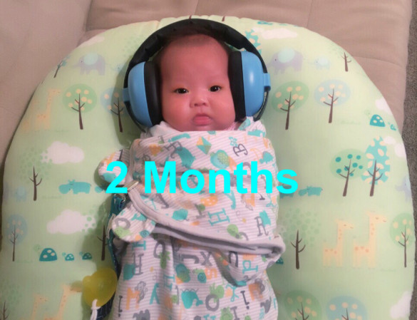 Carissa with her new Baby Banz noise canceling headphones at 2 months